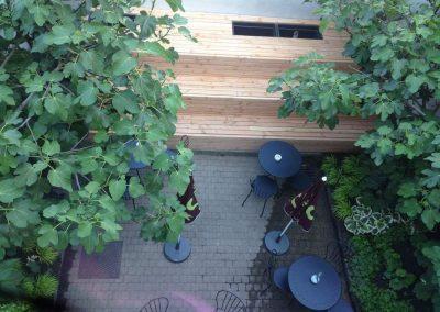 Stadstuin bij een eetterras in Gent: vijgenbomen zetten de toon, ondersteund door een weelderige schaduwbeplanting. Een gezellige groene plek voor een lunch of koffie (Folie à Deux, Gent)