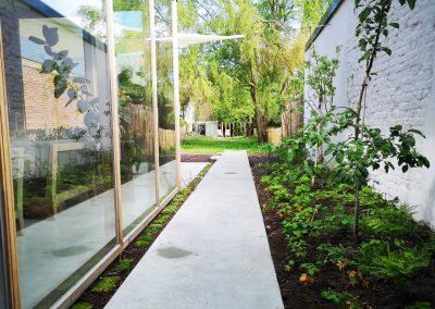 Gietbetonnen pad en terras. De betreedbare beplanting tussen beide oppervlakken contrasteert mooi met het harde betonnen oppervlak. Rechts een zone met laagstam fruitboompjes, kruiden en een mooie schaduwgemeenschap in de schaduwrijkere zones.