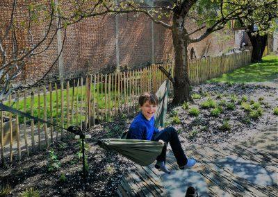 Deze pas aangelegde tuin ziet er nog wat kaal uit, maar de hangmat is nu al een schot in de roos! Onder dit rustplekje werd een leistenen terras met een organisch ontwerp aangelegd. Al vroeg in de lente is het hier heerlijk warm dankzij de westelijke oriëntatie in een ingesloten stadstuin.