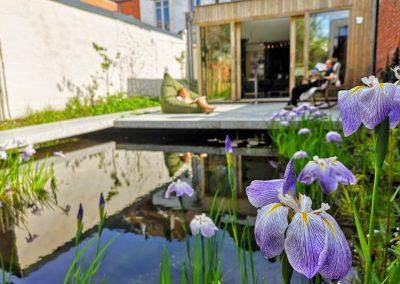 Dit betonnen terras zweeft boven de vijver. De vijverbeplanting bestaat uit een diverse gemeenschap, waarvan Irissen op dit tijdstip de show stelen. (In Bloom)